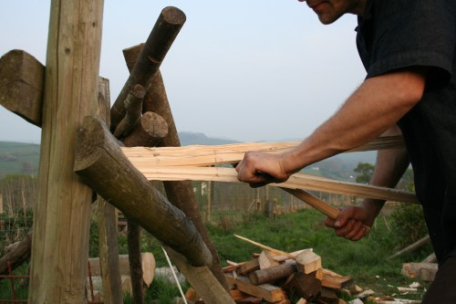Splitting wood along the grain by levering with a froe